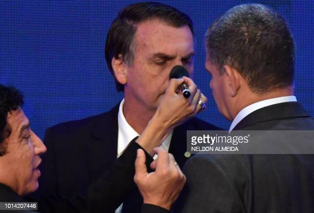 A makeup artist puts makeup on Brazilian presidential candidate Jair Bolsonaro as he listens to advisers before the start of the first presidential...