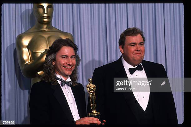 Makeup artist Rick Baker holds his Best Makeup Oscar for 'Harry and the Hendersons' while standing next to actor John Candy at the Academy Awards...