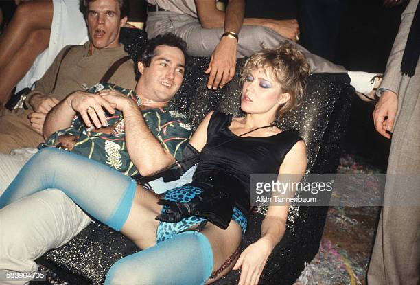 Makeup artist Sandy Linter dressed in a black satin relaxes tank top blue leopardprint underwear and blue stockings lies with one leg over an...