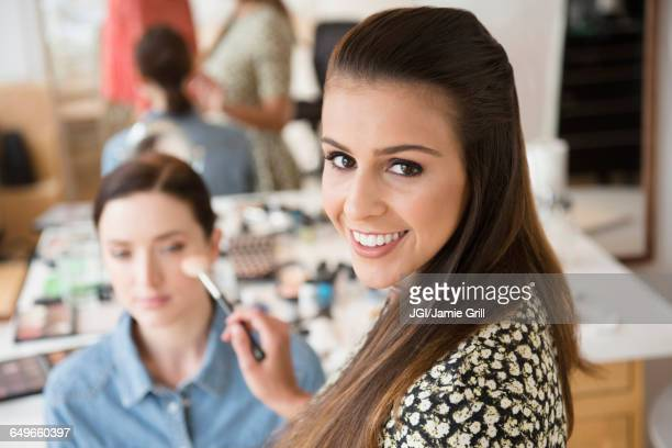 Makeup artist smiling with client