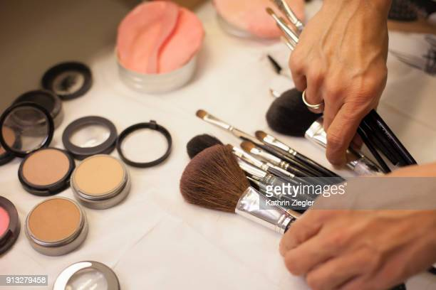 make-up artist sorting through brushes on the table - beautician stock pictures, royalty-free photos & images