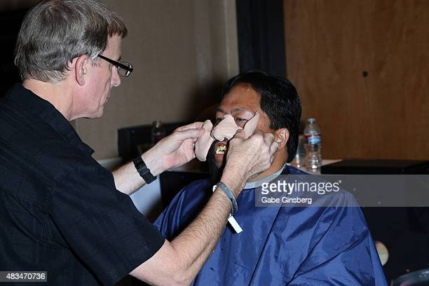 Makeup artist Tim Vittetoe applies a prosthetic face piece to Bill Arucan of California during the 14th annual official Star Trek convention at the...
