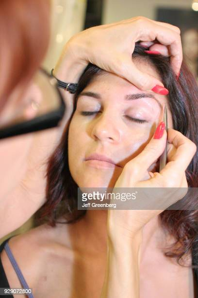 Makeup artist tweezing the eyebrows of a female model at Femme Coiffure.