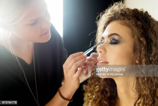 a make-up artist working on a model. - erin james stock-fotos und bilder