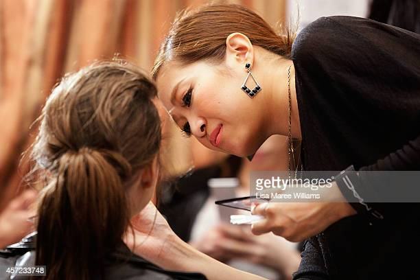 A makeup artist works on a model ahead of the LAMARCK show as part of Mercedes Benz Fashion Week TOKYO 2015 S/S at RISTORANTE ASO on October 15 2014...