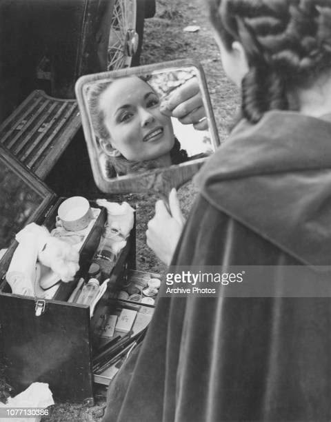 A makeup artist works on American actress Ann Blyth on the set of the 20th Century Fox film 'Man of Two Worlds' aka 'I'll Never Forget You' 1951