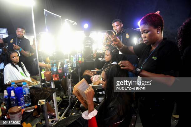Makeup artists prepare models for the runway during the Lagos Bridal Fashion Week in Lagos on May 4 2018
