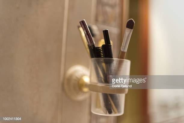 Make-up brushes and pencils in a plastic cup on a tiled wall