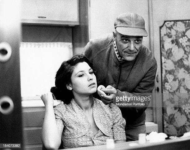 Make-up man putting foundation cream on the face of the Italian actress Lina Polito on the set of the film Salvo D'Acquisto. Rome, 1975