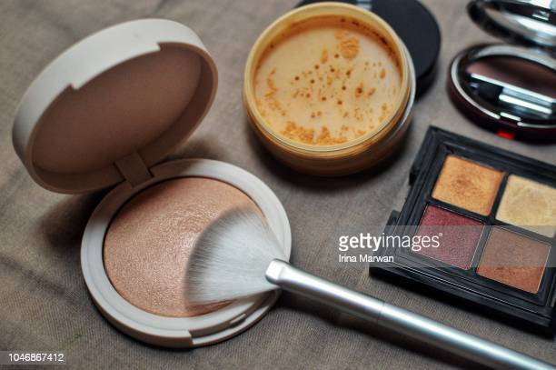 make-up products - highlighter, loose powder, and eyeshadow - stage make up stock photos and pictures