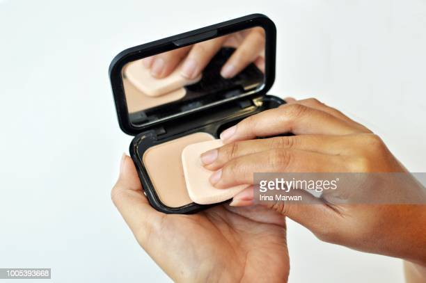 make-up: woman using compact face powder - foundation make up stock pictures, royalty-free photos & images