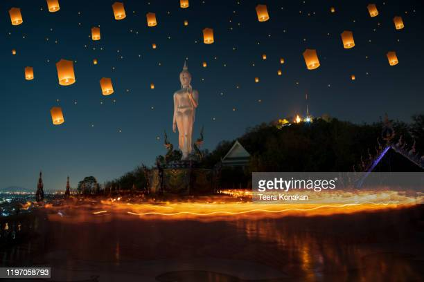 makha bucha day, candle lit from buddhists are moving around buddha statue at chonburi - yi peng stock pictures, royalty-free photos & images