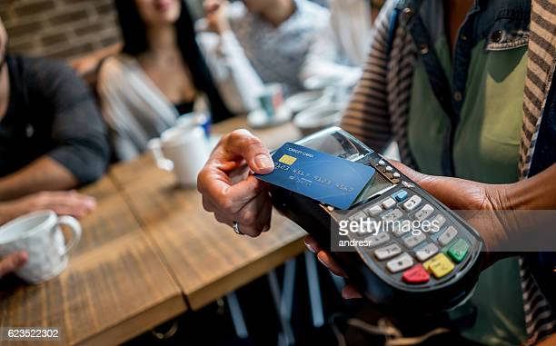 making a contactless payment at a restaurant - contactless payment stock pictures, royalty-free photos & images