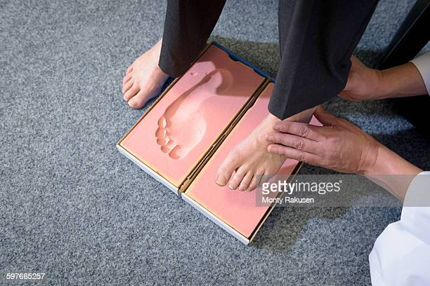 making a foot imprint mould for orthopaedic foot support - older woman bending over stock pictures, royalty-free photos & images