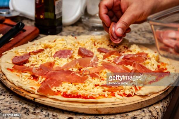making a homemade mixed pizza with raw ham and pepperoni - pepperoni pizza stock pictures, royalty-free photos & images