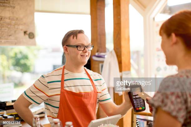 making a payment in the farm cafe - down syndrome stock pictures, royalty-free photos & images