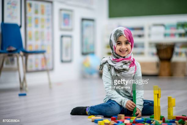 making a tower - muslim boy stock photos and pictures