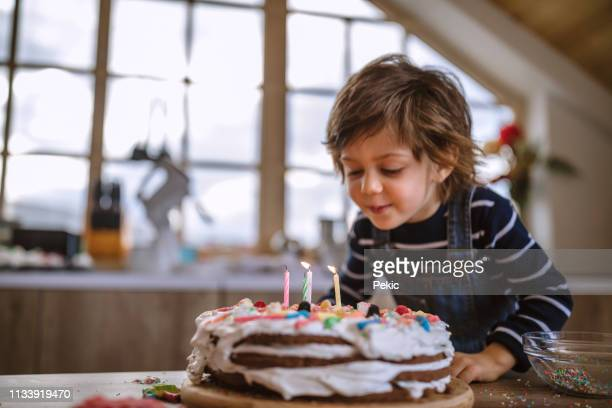 making a wish on his birthday - happy birthday stock pictures, royalty-free photos & images