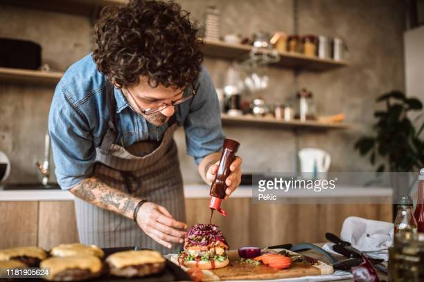 making a yummy burgers - sauce stock pictures, royalty-free photos & images