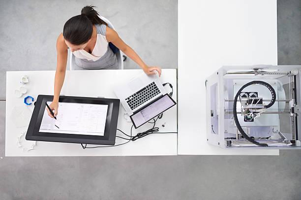Pessoa feminina fazendo um desenho técnico mecânico de maneira digital usando softwares
