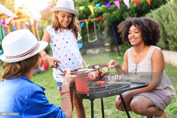making backyard barbecue - mother and daughter smoking stock photos and pictures