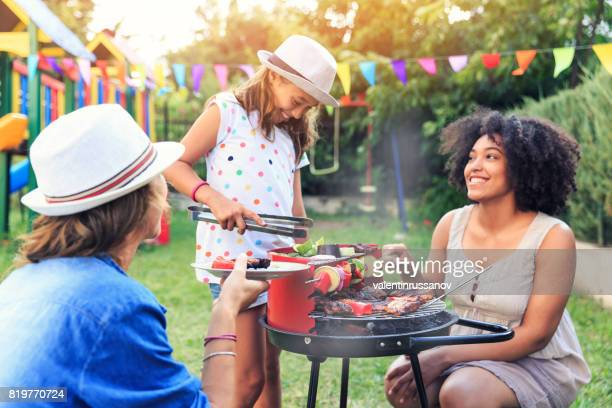 Making backyard barbecue with friends