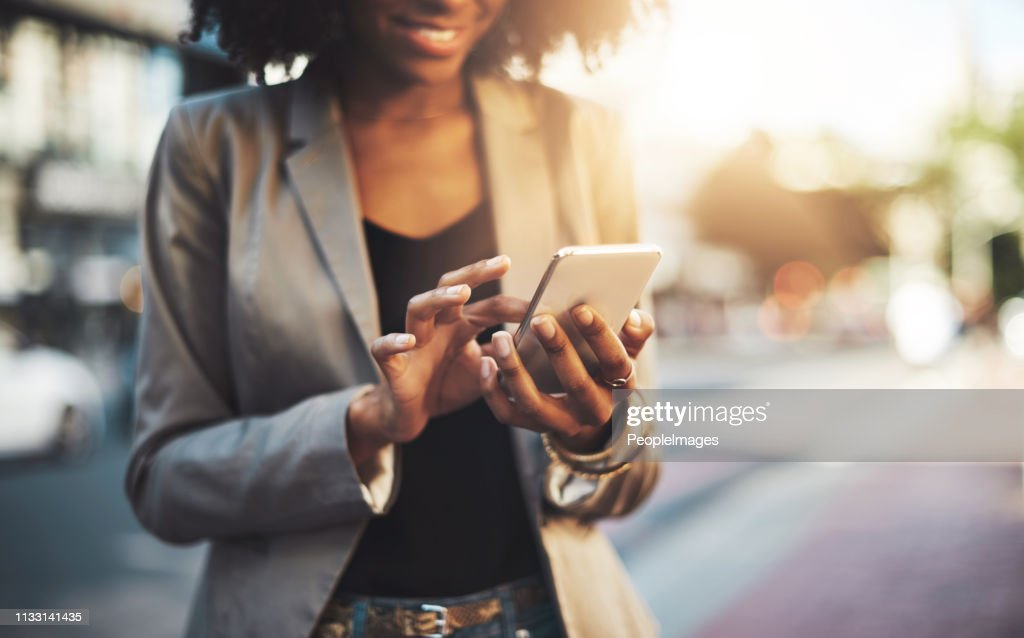Making big plans on her cellphone : Stock Photo