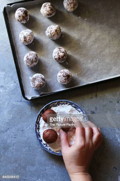 Making chocolate crinkle cookies.Female hand coating dough ball with icing sugar.Top view