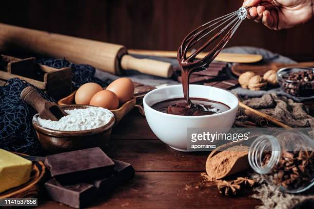 making chocolate mousse on a wooden table in a rustic kitchen - chocolate mousse stock pictures, royalty-free photos & images