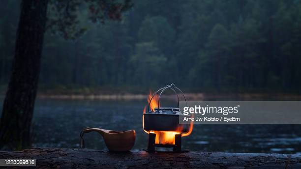 making coffee in the forests on a fire stove. a wooden kuksa cup waiting to be filled. - arne jw kolstø stock pictures, royalty-free photos & images