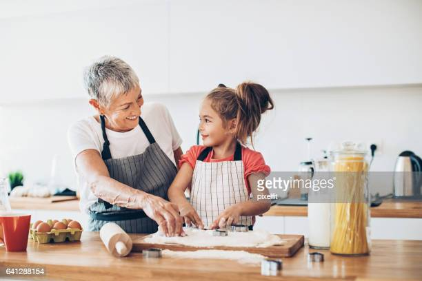 making cookies with grandma - grandmother stock pictures, royalty-free photos & images