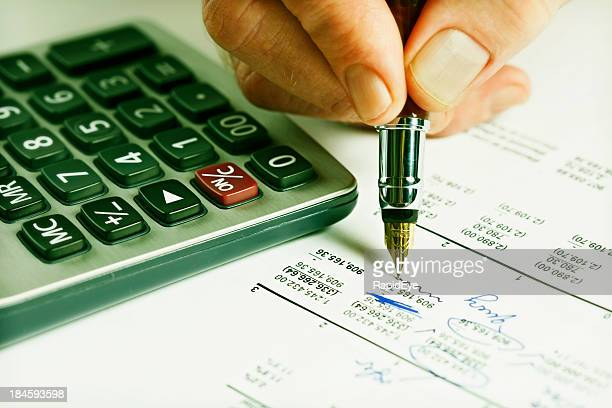 making corrections to spreadsheet with calculator and fountain pen - adjusting stock pictures, royalty-free photos & images