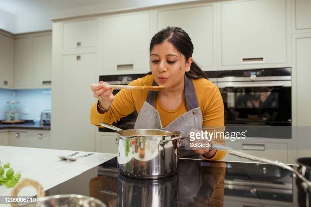 making curry in the kitchen - femalefocuscollection stock pictures, royalty-free photos & images