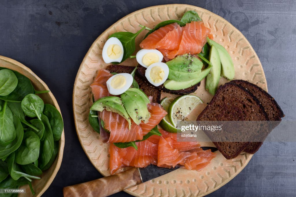 Making delicious toasts with  smoked salmon and fresh green vegetables : Stock Photo