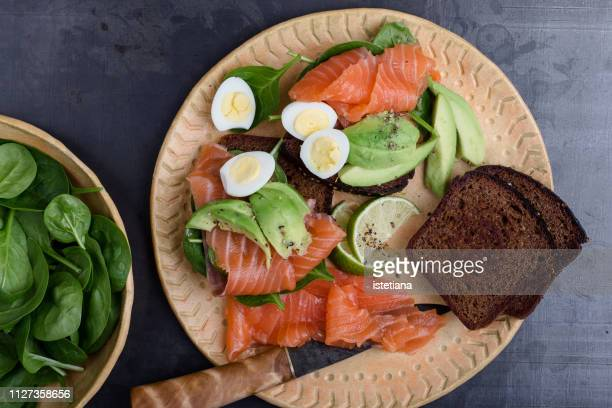 Making delicious toasts with  smoked salmon and fresh green vegetables