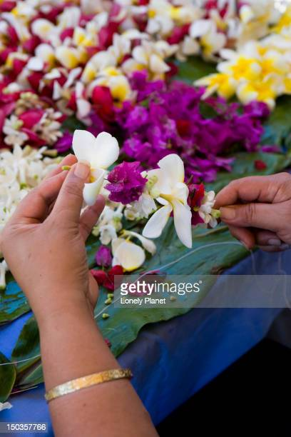 Making flower leis on a string.