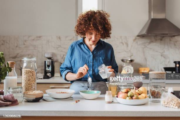making granola at home: woman adding coconut oil into a bowl with rolled oats and spices - coconut oil stock pictures, royalty-free photos & images