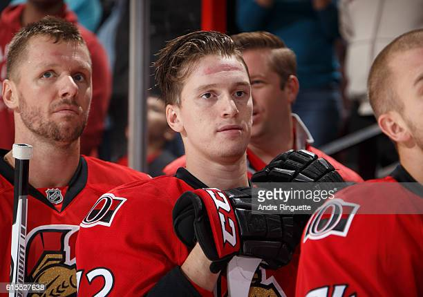 Making his NHL debut Thomas Chabot of the Ottawa Senators looks on from the bench during the singing of the national anthems prior to a game against...