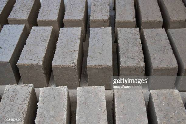 Making home made bricks for house construction. Newly prepared bricks sit in rows to dry.