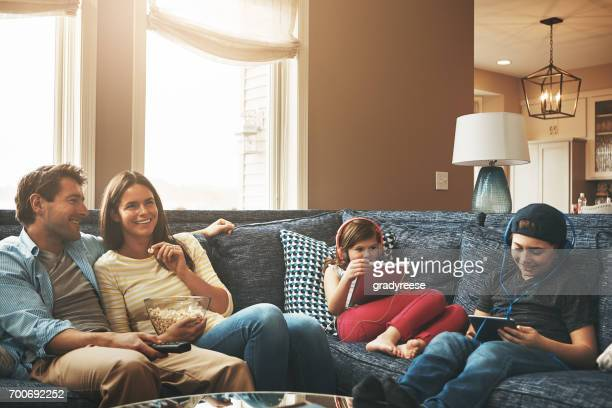 making it an exciting and entertaining weekend - family watching tv stock pictures, royalty-free photos & images