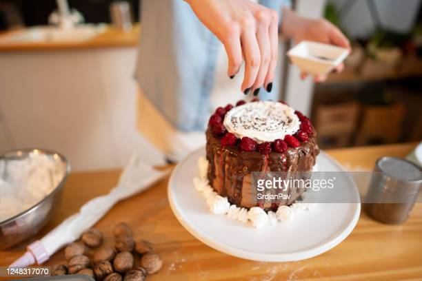 making it even more delicious - cake decoration stock pictures, royalty-free photos & images