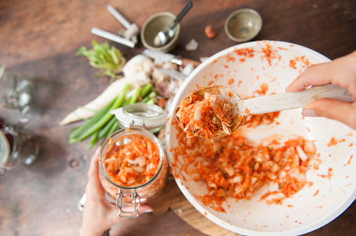 Making kimchi: putting the ingredients into a jar - gettyimageskorea