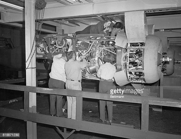 Making Liberators Willow Run Michigan Men and women workers fit a motor to a B24 Liberator bomber in the Ford Willow Run bomber plant which is now...