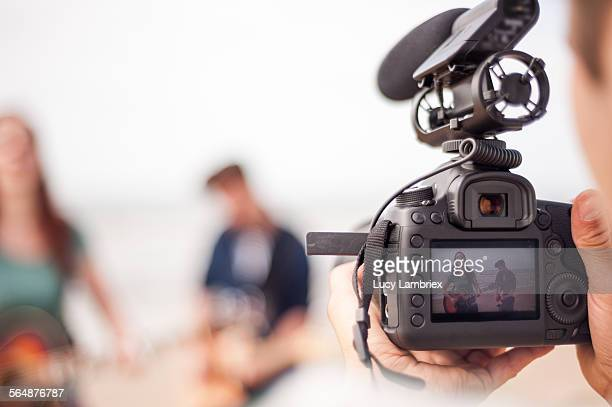 making of a videoclip on the beach - film crew stock photos and pictures