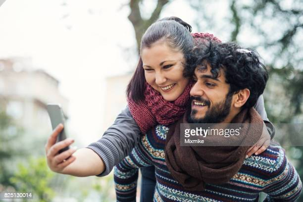 making selfies on the street - piggyback stock photos and pictures