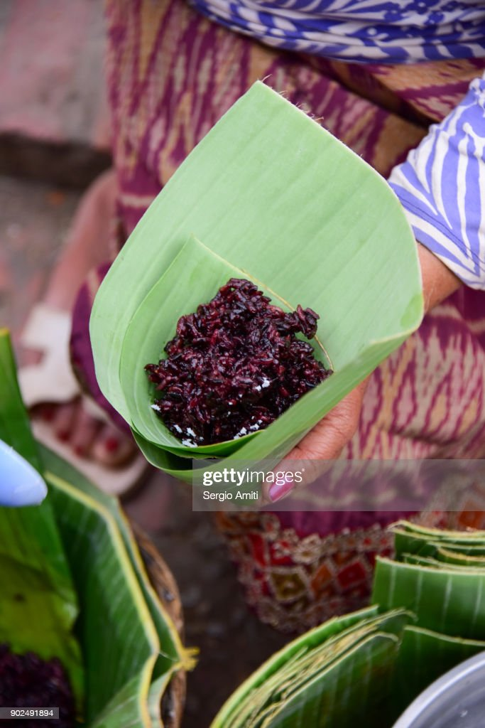 Making small parcels of bigo and rice with banana leaves : Stock-Foto