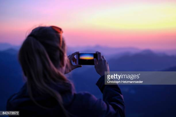 making smartphone photos on mountain - rear view photos stock photos and pictures