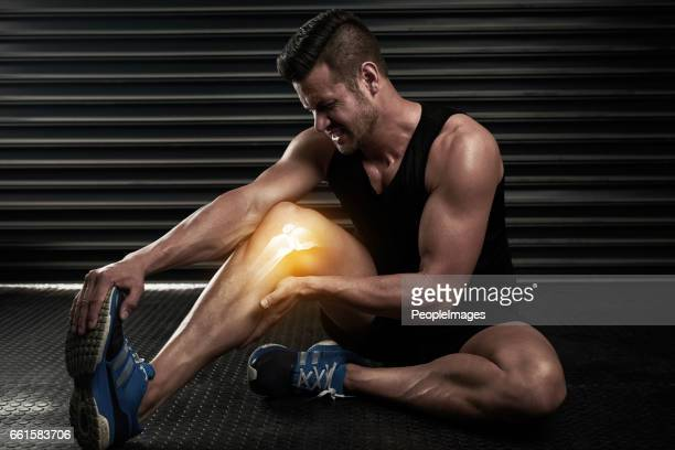 making sure he doesn't do further damage to his calf - personal injury stock photos and pictures