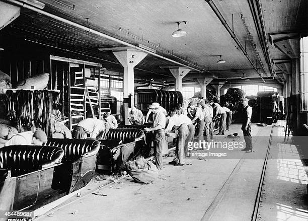 Making the bodies for Model T Fords 1915 Factory workers on the production line completing upholstery for the seats A sack of stuffing lies on the...