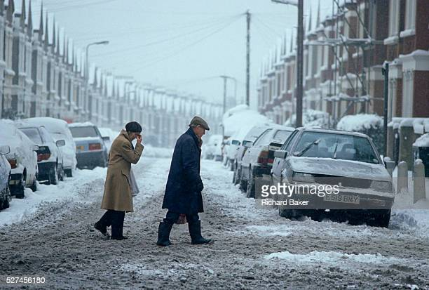 Making their way across a snowswept road in Norwood south London an elderly couple tread warily as the snow turns to slush It's a bleak raw morning...